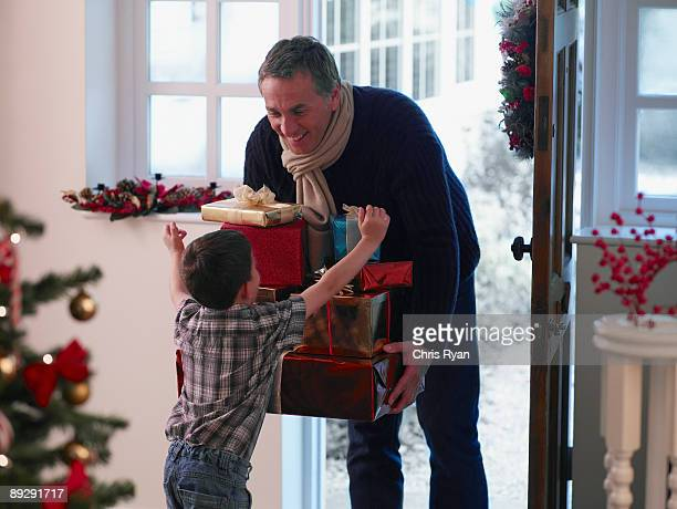 Boy running to father holding Christmas gifts in doorway