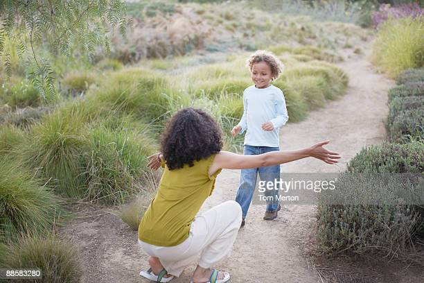 Boy running to mother on trail