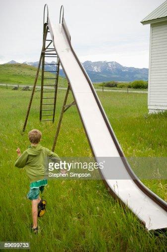Boy running to slide : Stock Photo