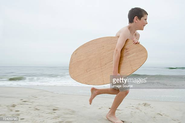 Boy running with boogie board