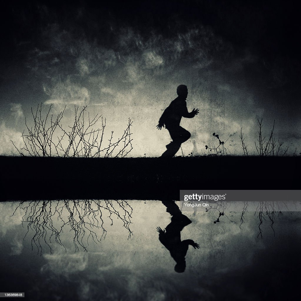 Boy running with reflection in lake : Stock Photo