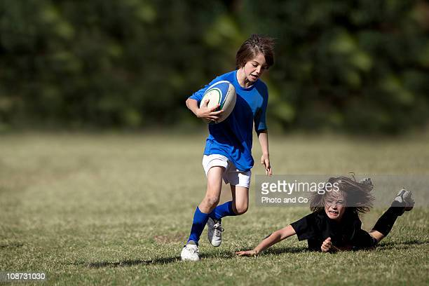 boy running with rugby ball pursued by opponent