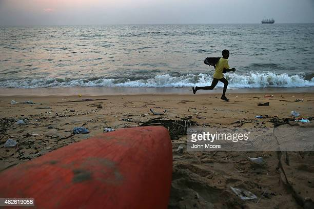 A boy runs along the Atlantic Ocean in the West Point township on January 31 2015 in Monrovia Liberia Life has slowly begun to return to normal for...