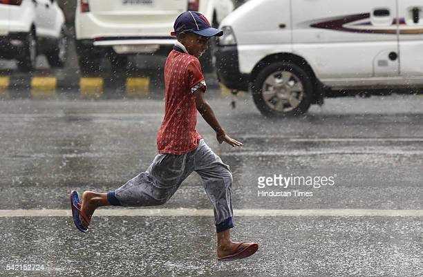 A boy runs as he is cought in showers at Connaught Place on June 22 2016 in New Delhi India A sudden spell of rain brought the temperatures down in...