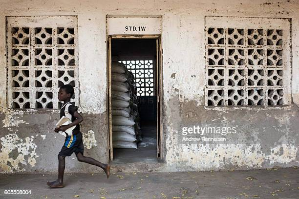 A boy runs by a classroom with bags of food aid at a school in the village of Malikopo which lies in one of the areas most affected by drought on...