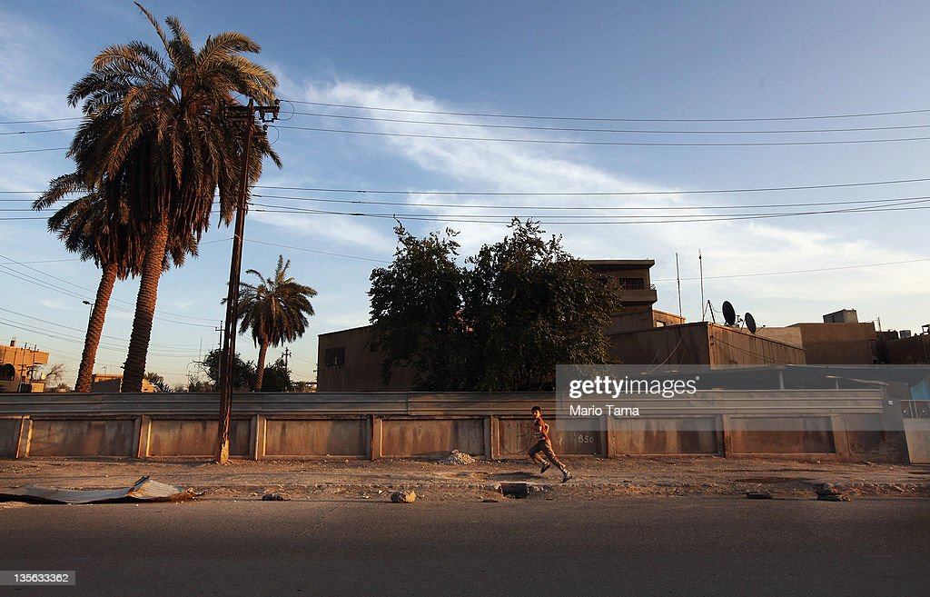 A boy runs down a street on December 12, 2011 in Baghdad, Iraq. Iraq is transitioning nearly nine years after the 2003 U.S. invasion and subsequent occupation. American forces are now in the midst of the final stage of withdrawal from the war-torn country. At least 4,485 U.S. military personnel have died in service in Iraq. According to the Iraq Body Count, more than 100,000 Iraqi civilians have died from war-related violence.