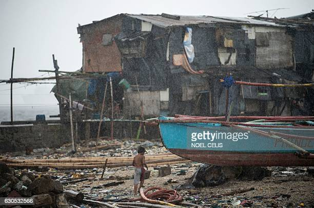 A boy runs for cover as it rains near the breakwater in Baseco Manila on December 26 2016 Typhoon NockTen which made landfall on the eastern island...