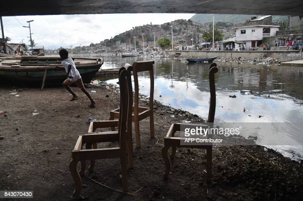 A boy runs next to Mapou River in Shadaa neighborhood in CapHaitien in the north of Haiti 240 km from PortauPrince ahead of Hurricane Irma on...