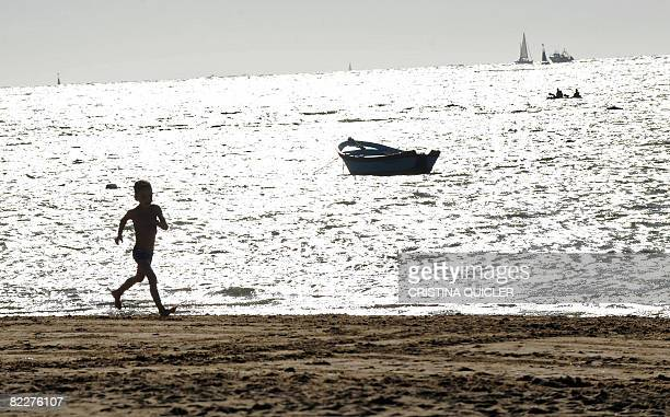 A boy runs on the beach during the traditional beach race of Sanlucar de Barrameda near Cadiz on August 12 2008 AFP PHOTO/ CRISTINA QUICLER