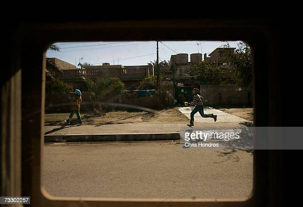 A boy runs on the sidewalk as seen through a US military Humvee window February 8 2007 in Baghdad Iraq The US military is short more than 4000 FRAG...