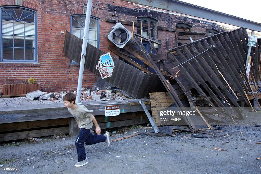 A boy runs past damage to the Chocolate Candy Manufacturing Company on the south side of downtown Seattle 28 February 2001 after an earthquake...