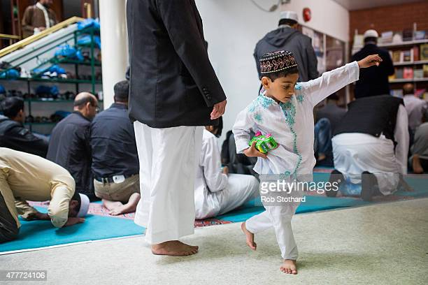 A boy runs through the East London Mosque as men arrive for the first Friday prayers of the Islamic holy month of Ramadan on June 19 2015 in London...