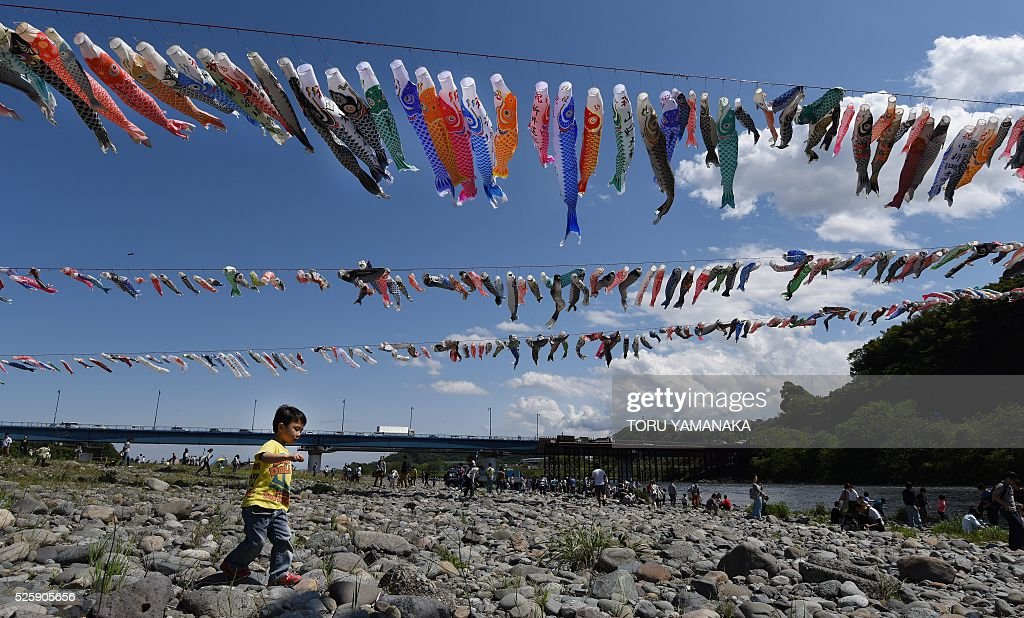 A boy runs under carp streamers fluttering in a riverside park in Sagamihara, suburban Tokyo, on April 29, 2016 ahead of May 5 Children's Day in Japan. Some 1,200 carp streamers were hoisted over the Sagami River to celebrate the annual holiday of Children's Day - part of Japan's 'Golden Week' holiday which is traditionally one of the busiest travel times of the year. / AFP / TORU