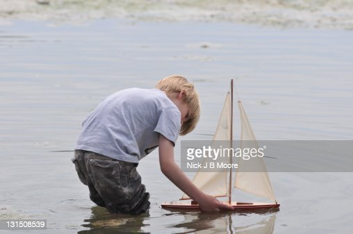 Lillle Boy Toys Boats : Boy sails toy boat stock photo getty images