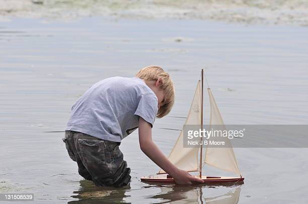 Boy sails toy boat