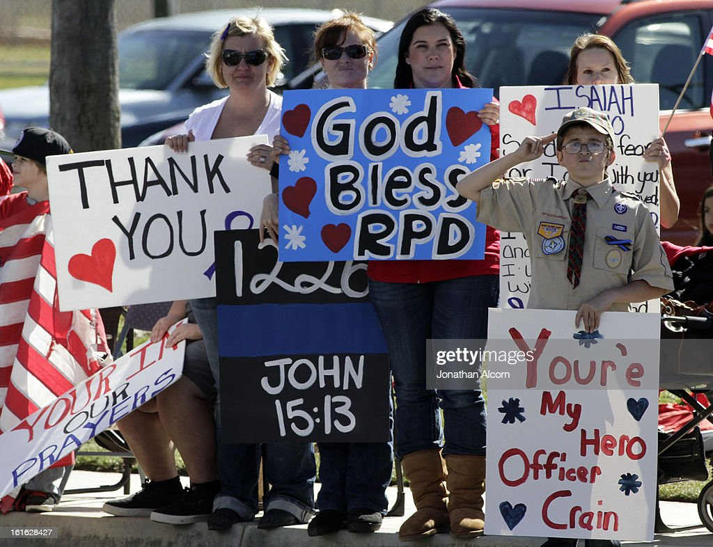 A boy salutes the procession of police vehicles leaving the funeral service for Riverside police Officer Michael Crain at Grove Community Church in Riverside, California, February 13, 2013. Officer Crain was allegedly killed by ex LAPD officer Chris Dorner on February 7, 2013.