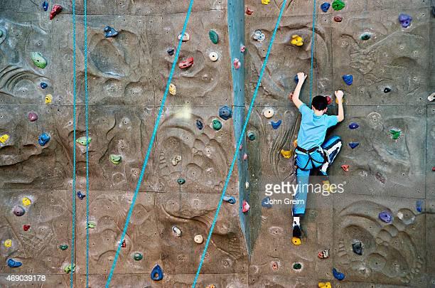Boy scaling an indoor rock climbing wall