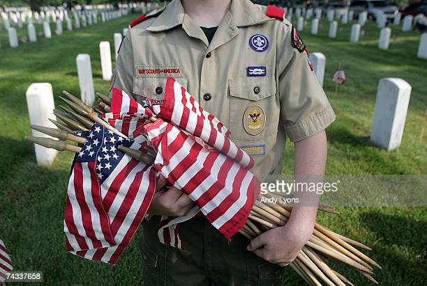 Boy Scout holds flags that are going to be placed on each grave at Zachary Taylor National Cemetery May 26 2007 in Louisville Kentucky Boy Scouts...