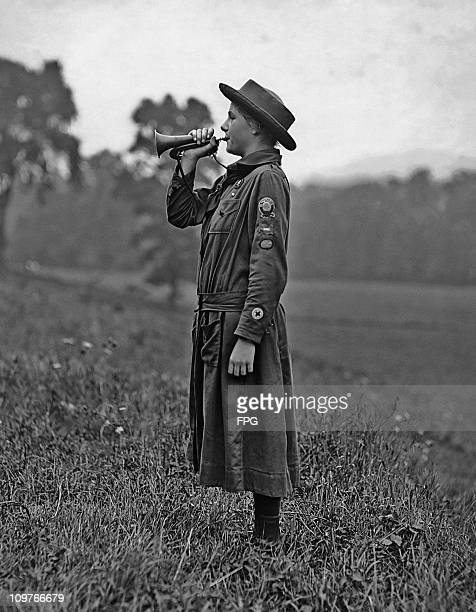 A Boy Scout playing a bugle in a field circa 1910