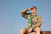 Young Boy Scout in Uniform Watching Over the Brown Field on A Sunny Day While Sitting on the Boulder.