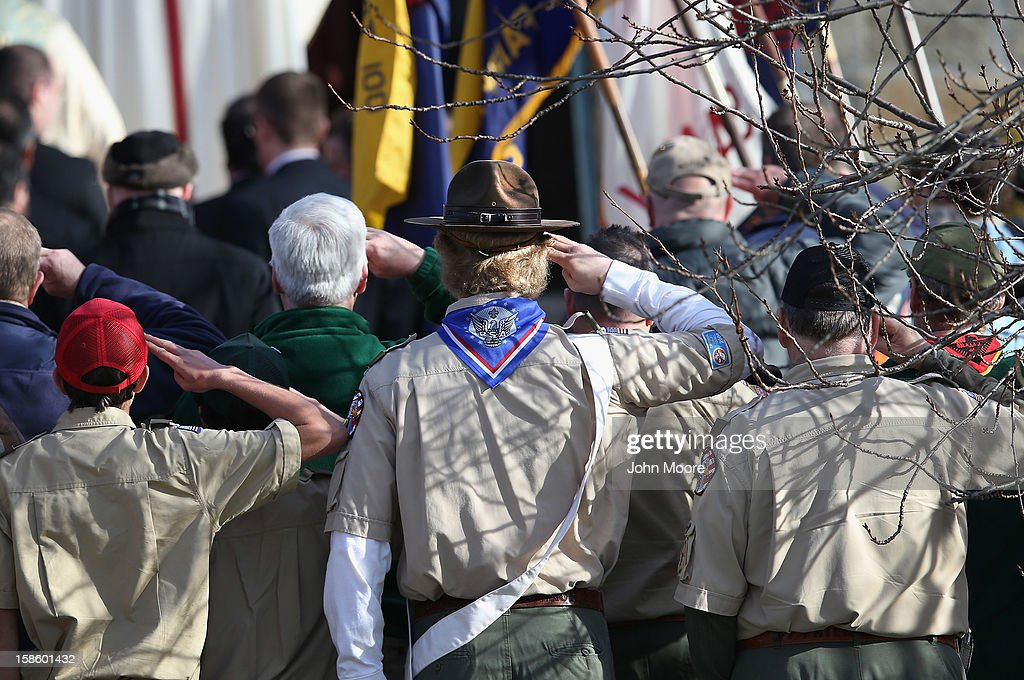 Boy scouts salute as a funeral procession for Benjamin Wheeler, 6, enters the Trinity Episcopal Church on December 20, 2012 in Newtown, Connecticut. Benjamin, a member of Tiger Scout Den 6, was killed when 20 children and six adults were massacred at Sandy Hook Elementary School last Friday.