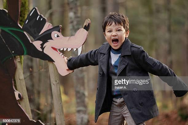 Boy screams pretending to be bitten by big wolf