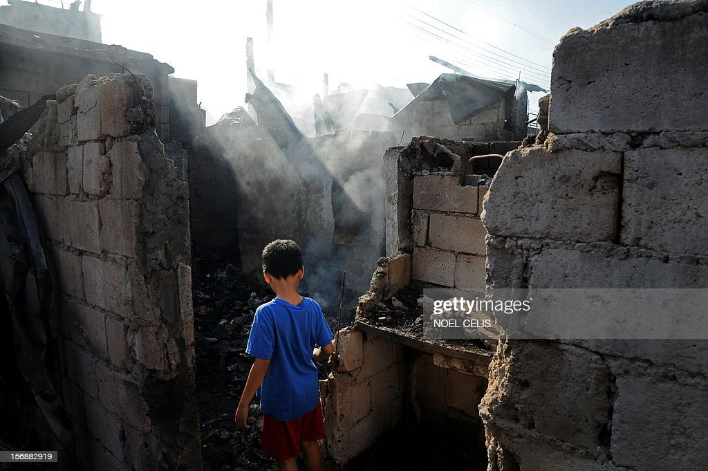 A boy searches for salvageable materials amongst the burnt debris of destroyed houses in Manila on November 24, 2012 after an overnight fire razed a slum area. Three children died during the fire and almost 150 people were affected according to local media report.