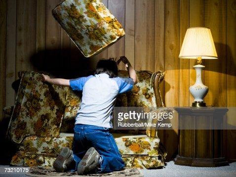 Boy searching under sofa cushions