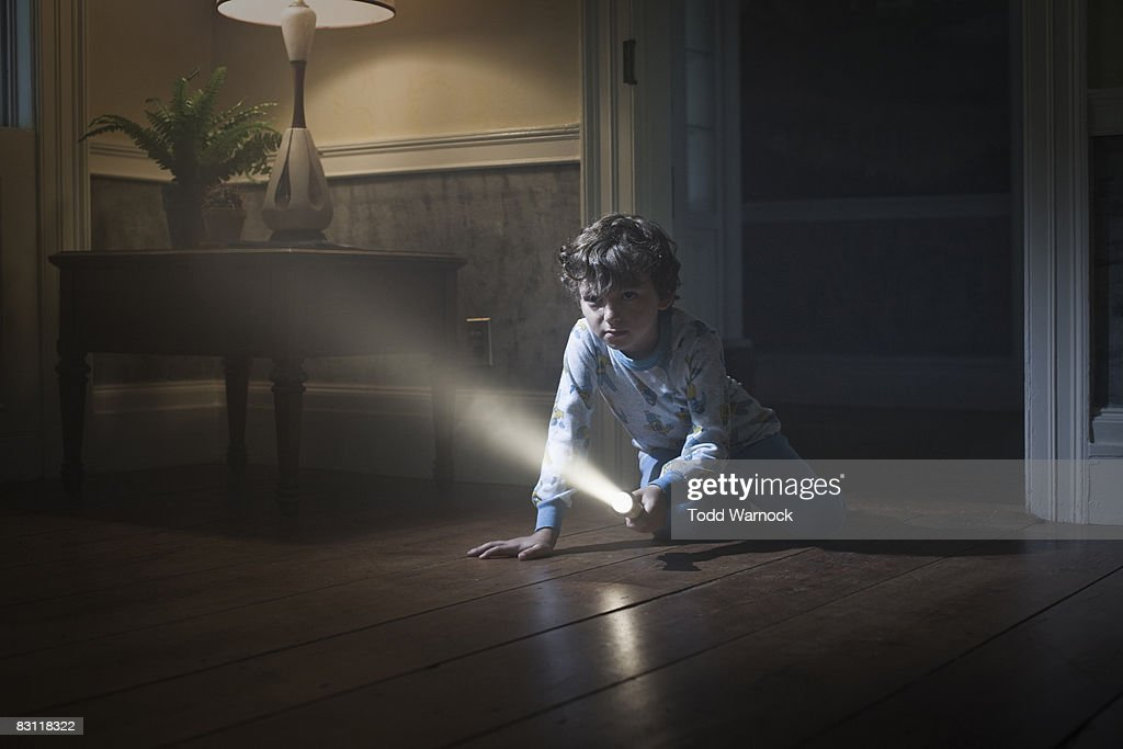 boy in pajamas on floor with flashlight, searching