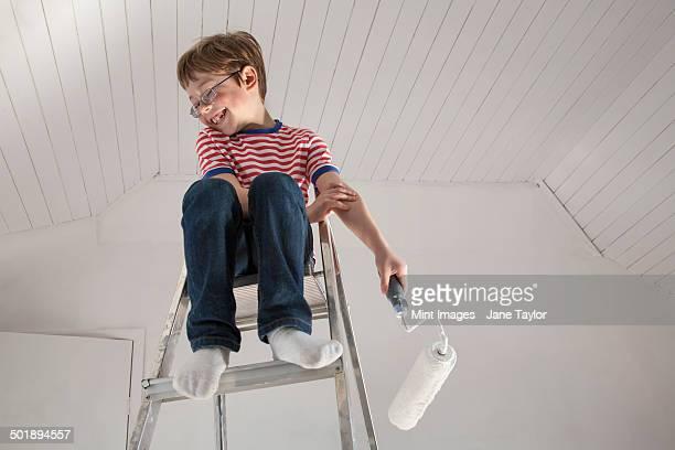 A boy seated on a stepladder.