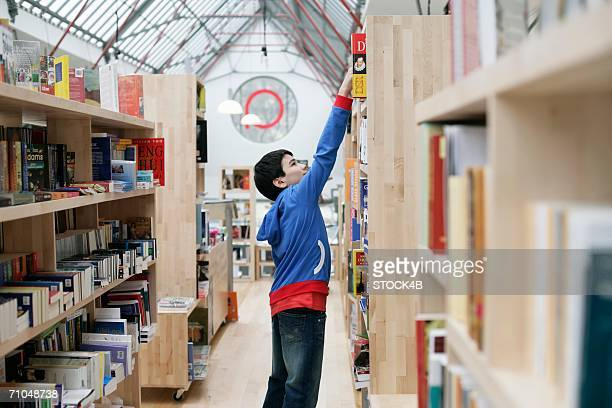 Boy selecting a book from a shelf