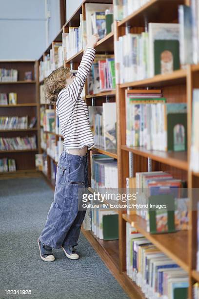 Boy selecting book from shelf in library