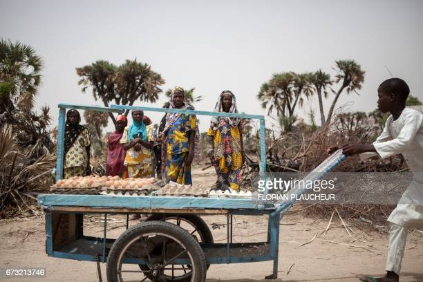 TOPSHOT A boy sells boiled eggs on the outskirt of the town of Damasak in North East Nigeria on April 25 2017 as thousands of Nigerians who were...