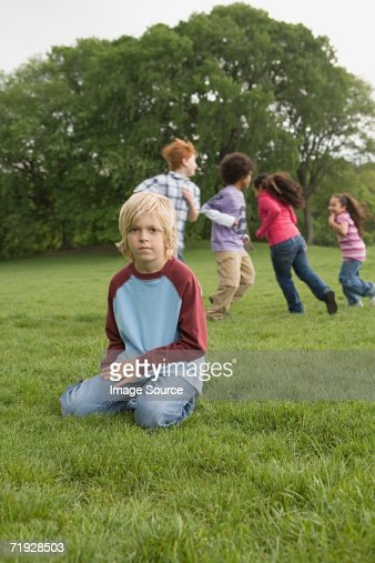Boy separate from other kids playing
