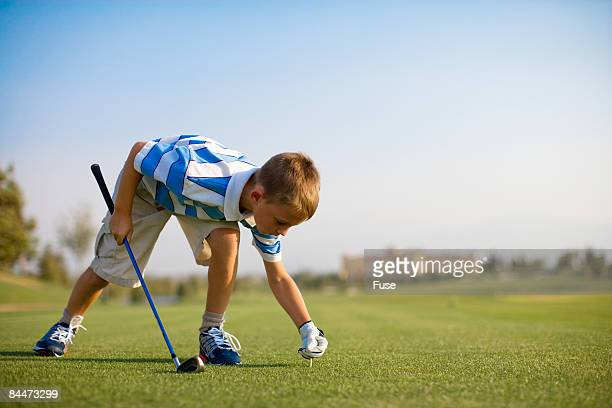 Boy Setting Ball on Tee