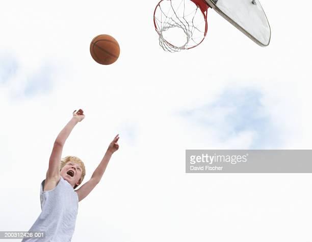 Boy (9-11) shooting basketball at basket, low angle view