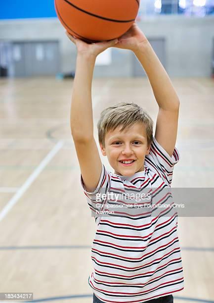 Boy (10-11) shooting basketball