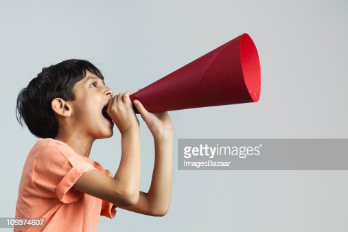 Boy (6-7) shouting through paper megaphone