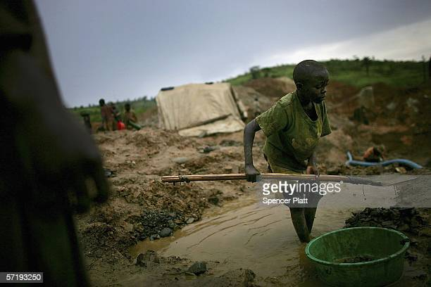 A boy shovels dirt into a bucket which will be sifted through while looking for gold March 27 2006 in Mongbwalu Congo Thousands of Congolese scrape...