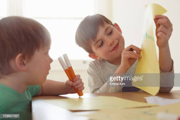 Boy showing brother drawing at table