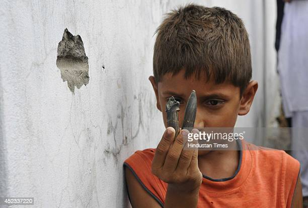 A boy showing bullets fired by Pakistani rangers as he stands near a bullet mark on wall at Pindee village near Pittal BSF Border Outpost in the...