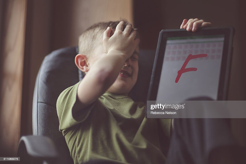 boy showing failing grade on electronic tablet : Stock Photo