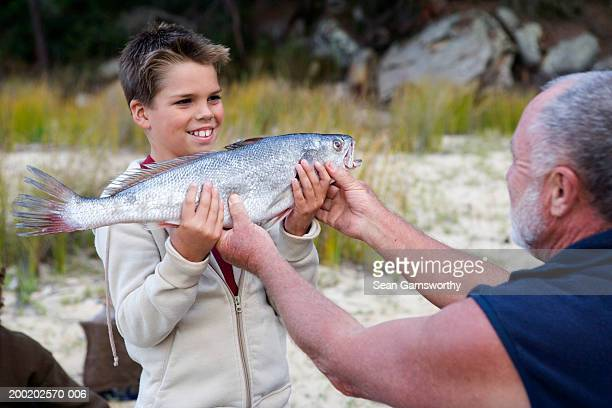 Boy (9-11) showing father fish, smiling, outdoors