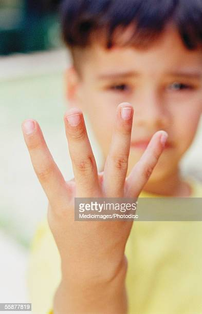 Boy showing four fingers