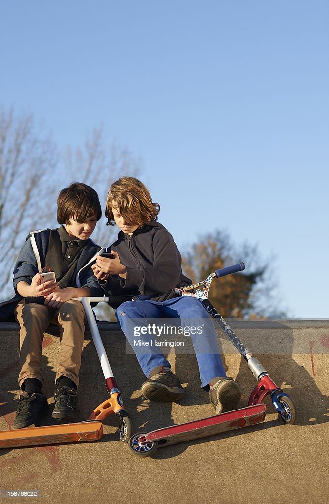 Boy showing friend mobile phone at skate park : Stock Photo