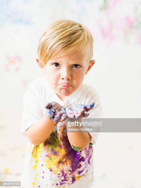 Boy (2-3) showing hands in paint