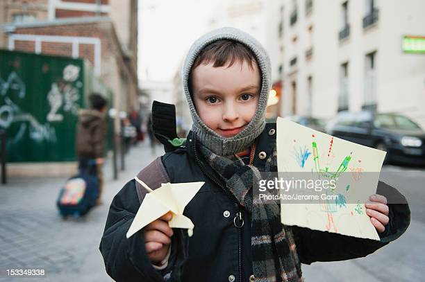Boy showing his drawing and origami crane