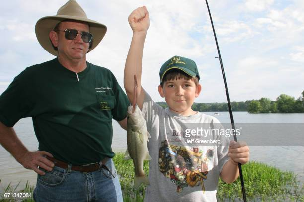 A boy showing off the fish he caught from Chattahoochee River