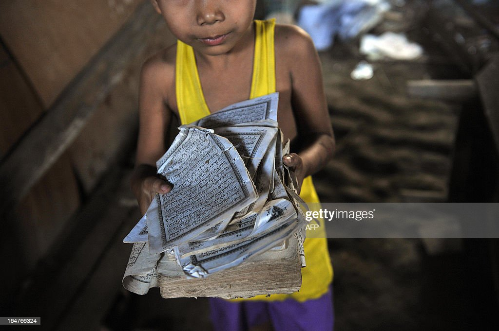 A boy shows the torn pages of a Koran at his ransacked house after sectarian violence spread through central Myanmar, in Zeegone, Bago division on March 28, 2013. A mosque and Muslim homes were destroyed by hundreds of people in the town of Zeegone about 150 kilometres (90 miles) north of the country's main city Yangon on March 27, the latest outbreak of violence in communal unrest that has left at least 40 people dead. AFP PHOTO/Ye Aung THU