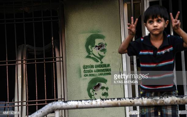 A boy shows vsign near a pictures of Kurdish jailed leader Abdullah Ocalan in central Diyarbakir on September 14 2015 Fifteen neighboroods in...